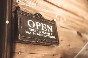 un cartello commerciale che dice aperto sulla porta all'ingresso foto