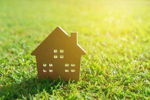 primo piano del piccolo modello di casa sull'erba con sfondo di luce solare foto