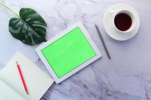 tavoletta digitale con caffè e un taccuino foto