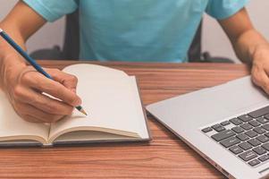 persona che scrive un libro a una scrivania foto