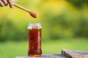 miele che gocciola dal mestolo di miele su sfondo naturale foto