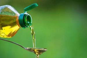 mano versando olio vegetale dalla bottiglia al cucchiaio foto