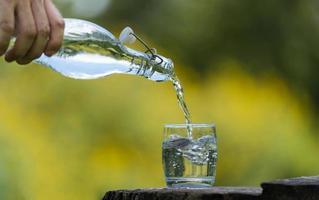 mano versando acqua potabile dalla bottiglia in vetro con sfondo naturale foto