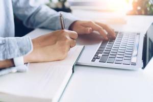 donna che scrive in un taccuino pianificatore durante l'utilizzo di laptop a casa foto