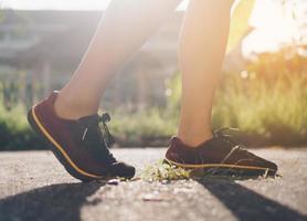 donna indossa scarpe da corsa e in esecuzione su sfondo verde natura foto