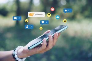 mano che tiene uno smartphone con icone di comunicazione foto