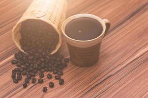 chicchi di caffè e tazza di caffè sul tavolo foto