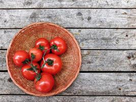 pomodori in un cesto di vimini su uno sfondo di tavolo in legno foto