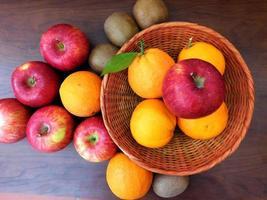 arance e mele in un cesto di vimini su uno sfondo di tavolo in legno scuro foto