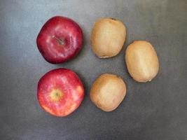 kiwi e mele su uno sfondo di tavolo in legno scuro foto