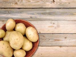 patate in un cesto di vimini su uno sfondo di tavolo in legno foto