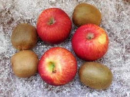 kiwi e mele su uno sfondo di fieno o paglia di plastica foto