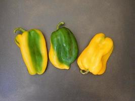 peperoni verdi e gialli su uno sfondo di tavolo scuro foto