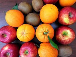 arance, kiwi e mele su uno sfondo di tavolo in legno scuro foto