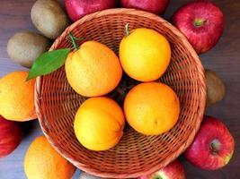 arance in un cesto di vimini accanto ad arance, kiwi e mele su uno sfondo di tavolo in legno scuro foto