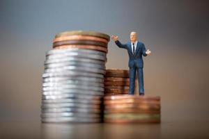 piccoli imprenditori in miniatura in piedi con una pila di monete, concetto di crescita del business foto