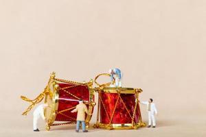 lavoratori in miniatura che dipingono una decorazione natalizia, natale e felice anno nuovo concetto foto