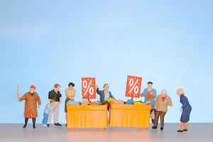 persone in miniatura che acquistano articoli scontati su un tavolo foto