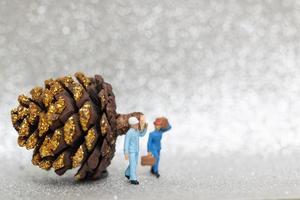 lavoratori in miniatura che preparano un concetto di pigna di natale, natale e felice anno nuovo foto