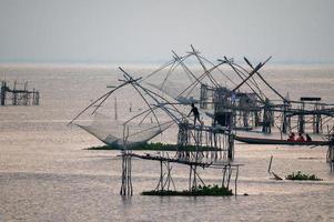 pescatori che pescano con una rete a pakpra, phatthalung, thailandia foto