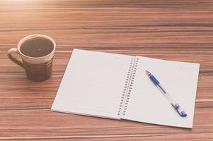 caffè e un blocco note sul tavolo di legno foto