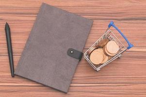 taccuino sulla scrivania con monete in un piccolo carrello foto