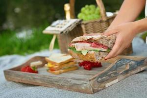 mano che tiene e mangiare un panino in una giornata di picnic foto
