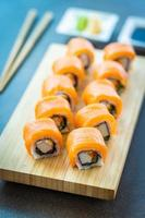 involtini di sushi di salmone sul piatto di legno