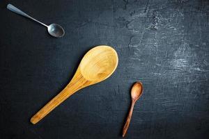 due cucchiai di legno e un cucchiaio di metallo su uno sfondo di tavolo nero foto