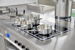 pentole in acciaio inox costruite sul fornello nella cucina del ristorante foto