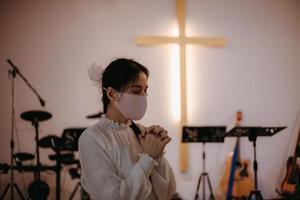 donna che indossa una maschera in chiesa foto