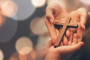 persona che consegna una croce di legno foto