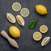 limoni e spremiagrumi su uno sfondo scuro foto