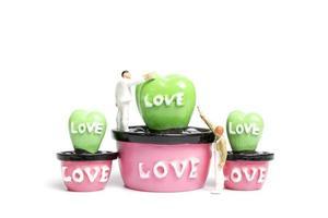 pittori in miniatura che colorano le piante in un baccello con la parola amore, il concetto di San Valentino