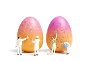 persone in miniatura che dipingono le uova di Pasqua per il giorno di Pasqua su uno sfondo bianco