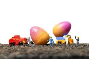 persone in miniatura che lavorano su uova di Pasqua per il giorno di Pasqua con uno sfondo bianco