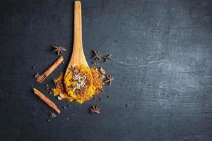 spezie colorate e polvere su un cucchiaio di legno su uno sfondo di tavolo nero foto