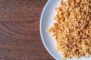 spaghetti istantanei su un piatto bianco su un tavolo di legno foto