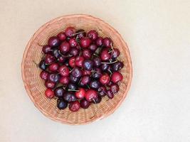 ciliegie in un cesto di vimini isolato su uno sfondo di tavolo beige foto
