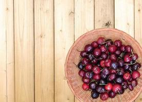 ciliegie in un cesto di vimini isolato su uno sfondo di tavolo in legno foto