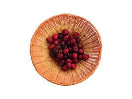 ciliegie in un cesto di vimini isolato su uno sfondo bianco foto