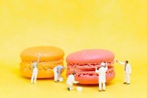 pittori in miniatura che colorano amaretti su uno sfondo giallo foto