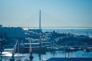 paesaggio marino con una vista di un porto e il ponte russky contro un cielo blu chiaro a vladivostok, russia foto