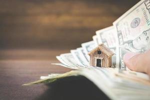 denaro e modello di casa su un fondo in legno, finanza e concetto bancario foto