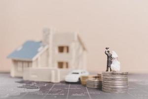 sposa e sposo in miniatura con monete davanti a una casa, concetto di famiglia di successo foto