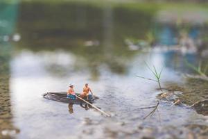 pescatori in miniatura che pescano su una barca foto