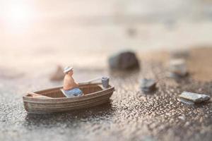 pescatore in miniatura che pesca su una barca foto