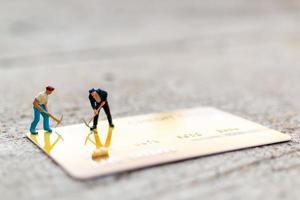 lavoratori in miniatura che lavorano su una carta di credito, affari e concetto di finanza foto