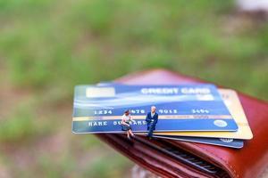 imprenditori in miniatura seduti su una carta di credito, concetti di affari e finanza foto