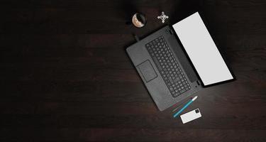 Illustrazione 3D di legno scuro con computer portatile, penna, telefono e forniture, vista dall'alto foto